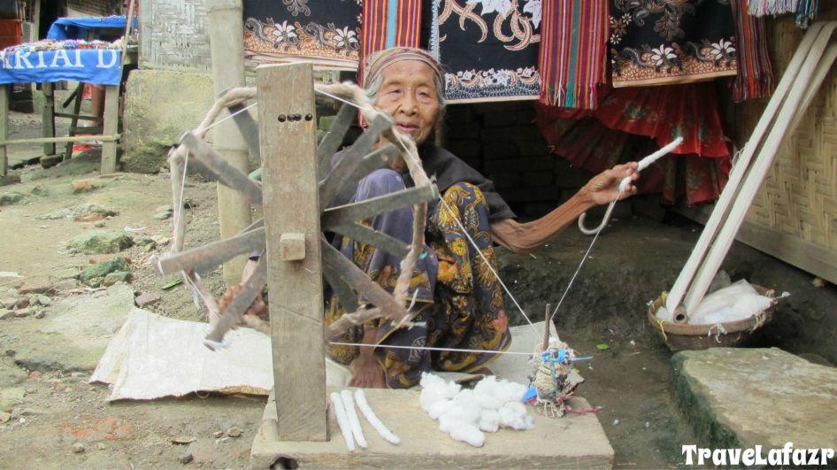 Nenek ini sedang memintal kapas untuk menghasilkan benang dengan alat pintal tradional