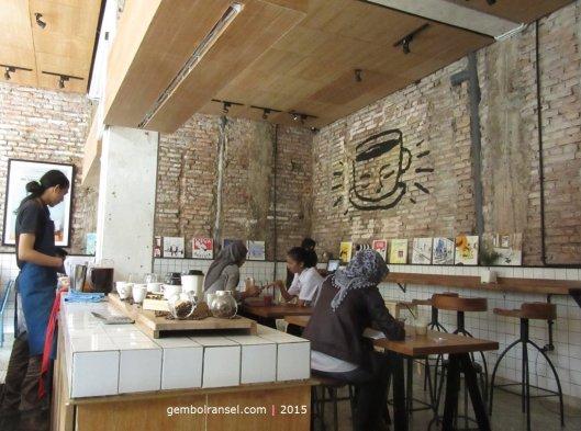 Dinding bata merah dan material kayu mendominasi interior kedai
